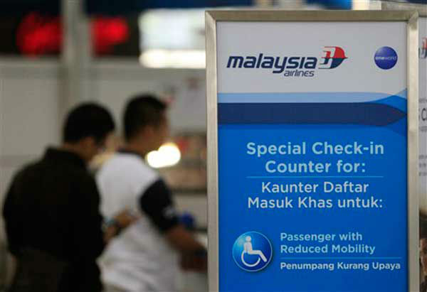 Passengers check in at a Malaysia Airlines counter at Kuala Lumpur International Airport in Sepang, Malaysia, Sunday, March 9, 2014. Vietnamese ships and planes hunting for a missing Malaysian jetliner have found no wreckage close to where they spotted two large oil slicks. The Boeing 777 carrying 239 people disappeared off radar screens early Saturday less than an hour after taking off from Kuala Lumpur bound for Beijing. (AP Photo/Lai Seng Sin)