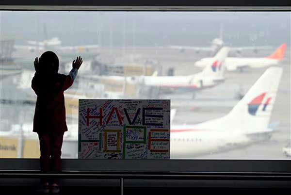 A girl stands next to a sign board made and written by the public at Kuala Lumpur International Airport in Sepang, Malaysia, Monday, March 10, 2014. Vietnamese aircraft spotted what they suspected was one of the doors of the missing Boeing 777 on Sunday, while questions emerged about how two passengers managed to board the ill-fated aircraft using stolen passports. &#40;AP Photo&#47;Daniel Chan&#41; <span class=meta>(Photo&#47;Daniel Chan)</span>