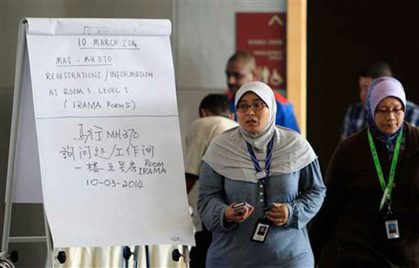 Employees of Malaysia Airlines walk past a notice board for families and friends of passengers aboard a missing Malaysia Airlines plane at a hotel in Putrajaya, Malaysia, Monday, March 10, 2014. Vietnamese aircraft spotted what they suspected was one of the doors of the missing Boeing 777 on Sunday, while questions emerged about how two passengers managed to board the ill-fated aircraft using stolen passports. &#40;AP Photo&#47;Lai Seng Sin&#41; <span class=meta>(Photo&#47;Lai Seng Sin)</span>