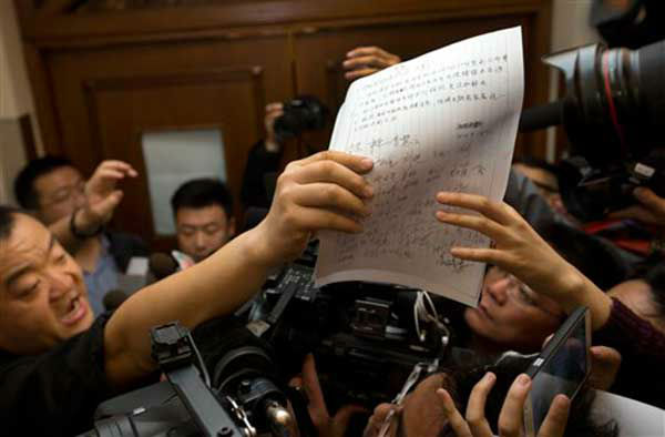 A Chinese relative of the passengers aboard the missing Malaysia Airlines plane passes a demand letter for the airlines, signed by other relatives, to the media at a hotel, in Beijing, China Sunday, March 9, 2014. Military radar indicates that the missing Boeing 777 jet turned back before vanishing, Malaysia&#39;s air force chief said Sunday as authorities were investigating up to four passengers with suspicious identifications who may have boarded the flight. &#40;AP Photo&#47;Andy Wong&#41; <span class=meta>(Photo&#47;Andy Wong)</span>