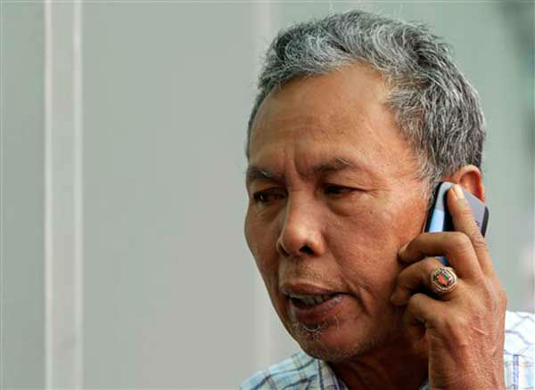 A family member of passengers aboard a missing Malaysia Airlines plane talks on his mobile phone at a hotel in Putrajaya, Malaysia, Monday, March 10, 2014. Vietnamese aircraft spotted what they suspected was one of the doors of the missing Boeing 777 on Sunday, while questions emerged about how two passengers managed to board the ill-fated aircraft using stolen passports. &#40;AP Photo&#47;Lai Seng Sin&#41; <span class=meta>(Photo&#47;Lai Seng Sin)</span>