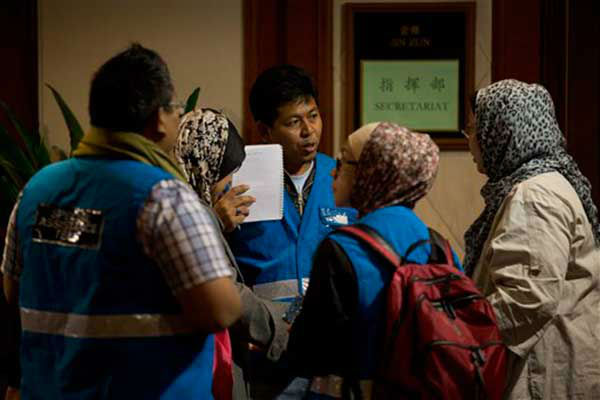 Members of a special assistance team from Malaysia chat at a hotel prepared for relatives or friends of passengers aboard a missing Malaysian Airlines jetliner, in Beijing, China Sunday, March 9, 2014. Planes and ships from across Asia resumed to the hunt Sunday for a Malaysian jetliner missing with 239 people on board for more than 24 hours, while Malaysian aviation authorities investigated how two passengers were apparently able to get on the aircraft using stolen passports. &#40;AP Photo&#47;Andy Wong&#41; <span class=meta>(Photo&#47;Andy Wong)</span>