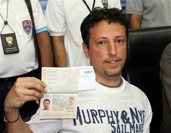 Italian Luigi Maraldi, left, whose stolen passport was used by a passenger boarding a missing Malaysian airliner, shows his passport as he reports himself to Thai police at Phuket police station in Phuket province, southern Thailand Sunday, March 9, 2014. Maraldi spoke at a police news conference where he showed his current passport, which replaced the stolen one, and expressed surprise that anyone could use his old one. &#40;AP Photo&#47;Krissada Muanhawang&#41; <span class=meta>(Photo&#47;Krissada Muanhawong)</span>