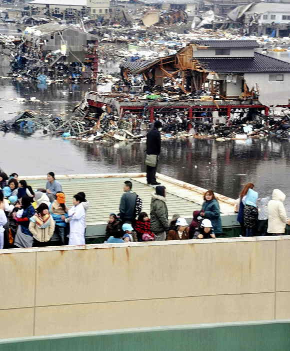 People evacuated to a rooftop of a building look at other buildings damaged by tsunami tidal waves at a port in Kesennuma in Miyagi Prefecture, northern Japan, after strong earthquakes hit the area Friday, March 11, 2011.  <span class=meta>(AP Photo&#47;Keichi Nakane, The Yomiuri Shimbun)</span>
