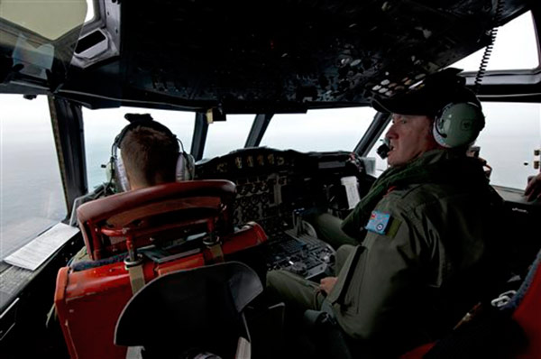 This Wednesday, March 19, 2014 photo released by the Australia Defence Department, shows Royal Australian Air Force Flight Engineer, Warrant Officer Ron Day from 10 Squadron, on board an AP-3C Orion over the Southern Indian Ocean off the Western Australian coast during a search operation for the missing Malaysian Airlines flight MH370. Australian Prime Minister Tony Abbott said Thursday that two objects possibly related to the missing flight have been spotted on satellite imagery in the Indian Ocean and an air force aircraft was diverted to the area to try to locate them.  <span class=meta>(AP Photo&#47;Australia Defence Department, Hamish Paterson)</span>