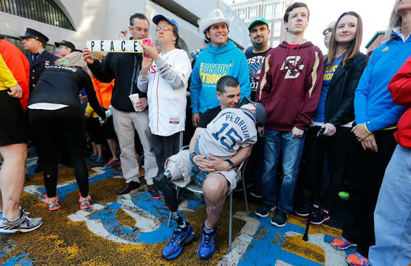 Boston Marathon bombing survivor Marc Fucarile, seated, talks to his son Gavin, 6, at the finish line of the Boston Marathon in Boston, Saturday, April 12, 2014. At least 2000 people, including survivors and first-responders showed up to participate in a Sports Illustrated photo shoot to commemorate the one-year anniversary of the bombings.  <span class=meta>(AP Photo&#47; Michael Dwyer)</span>