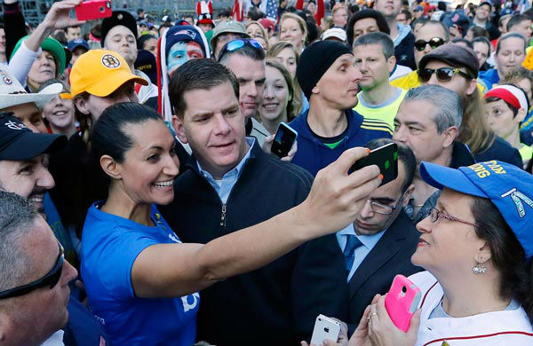 Boston Mayor Marty Walsh poses for a selfie at the finish line of the Boston Marathon in Boston, Saturday, April 12, 2014. The mayor joined a crowd gathered for a Sports Illustrated photo shoot to commemorate the one-year anniversary of the Boston Marathon bombing.  <span class=meta>(AP Photo&#47; Michael Dwyer)</span>
