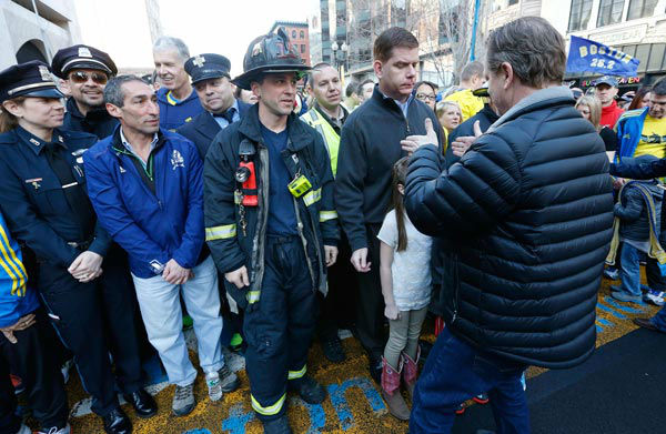"<div class=""meta ""><span class=""caption-text "">A member of the Sports Illustrated crew positions Boston Mayor Marty Walsh, center right, during a photo shoot at the finish line of the Boston Marathon in Boston, Saturday, April 12, 2014. The mayor, along with survivors, first-responders and at least 2000 other participants posed for a proposed cover photo to commemorate the one-year anniversary of the Boston Marathon bombings.  (AP Photo/ Michael Dwyer)</span></div>"