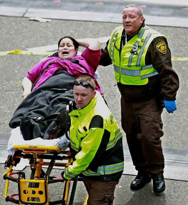 Medical workers aid an injured woman at the finish line of the 2013 Boston Marathon following two explosions there, Monday, April 15, 2013 in Boston. Two bombs exploded near the finish of the Boston Marathon on Monday, killing at least two people, injuring at least 23 others and sending authorities rushing to aid wounded spectators.  <span class=meta>(AP Photo&#47;Charles Krupa)</span>
