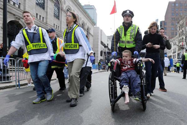 "<div class=""meta ""><span class=""caption-text "">A Boston police officer wheels in injured boy down Boylston Street as medical workers carry an injured runner following an explosion during the 2013 Boston Marathon in Boston, Monday, April 15, 2013. Two explosions shattered the euphoria at the marathon's finish line on Monday, sending authorities out on the course to carry off the injured while the stragglers were rerouted away from the smoking site of the blasts.  (AP Photo/Charles Krupa)</span></div>"