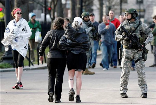 "<div class=""meta ""><span class=""caption-text "">As Boston Marathon runners walk by, SWAT team members stand guard near the finish line in Boston Monday, April 15, 2013. Two explosions shattered the euphoria of the Boston Marathon finish line on Monday, sending authorities out on the course to carry off the injured while the stragglers were rerouted away from the smoking site of the blasts.  (AP Photo/Winslow Townson)</span></div>"