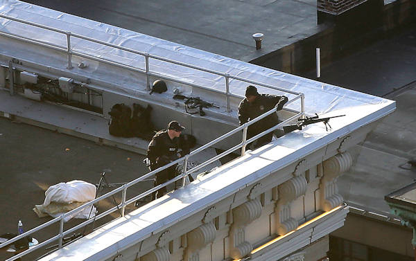 "<div class=""meta ""><span class=""caption-text "">Two police officers have rifles and watch from the roof of the Lenox Hotel overlooking the finish area of the 2013 Boston Marathon in Boston Monday, April 15, 2013.  (AP Photo/Elise Amendola)</span></div>"