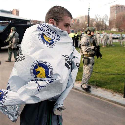 "<div class=""meta ""><span class=""caption-text "">Boston Marathon runner Russell Clifford of Marlborough, Mass. walks past SWAT officers near the finish line of the Boston Marathon in Boston Monday, April 15, 2013. Two explosions shattered the euphoria of the Boston Marathon finish line on Monday, sending authorities out on the course to carry off the injured while the stragglers were rerouted away from the smoking site of the blasts. (AP Photo/Winslow Townson)</span></div>"