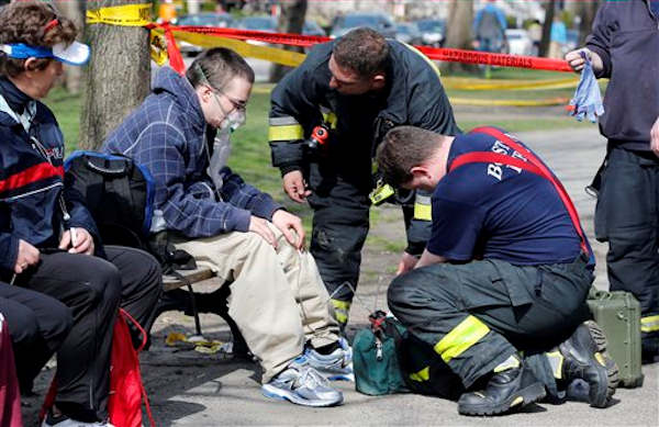 Firefighters tend to a man following an explosion at the finish line of the Boston Marathon in Boston, Monday, April 15, 2013. Two bombs exploded at the Boston Marathon finish line Monday killing at least two people injuring dozens. <span class=meta>(AP Photo&#47;Michael Dwyer)</span>