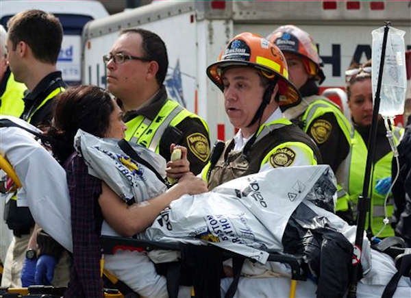 Emergency responders aid a woman on a stretcher who was injured in a bomb blast near the finish line of the Boston Marathon Monday, April 15, 2013 in Boston.  <span class=meta>(AP Photo&#47;Jeremy Pavia)</span>