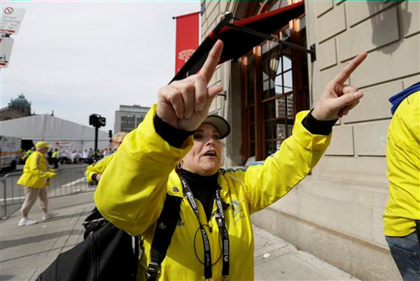 A Boston Marathon volunteer asks people to leave the area outside the Copley Plaza Hotel in the aftermath of two blasts which exploded near the finish line of the Boston Marathon in Boston, Monday, April 15, 2013.  <span class=meta>(AP Photo&#47;Elise Amendola)</span>