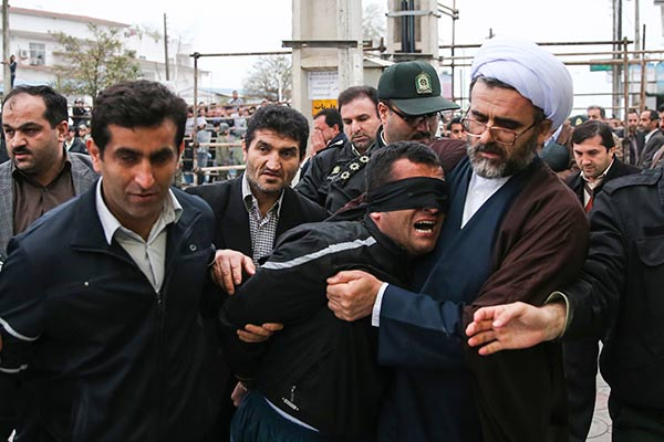 "<div class=""meta ""><span class=""caption-text "">This picture provided by ISNA, a semi-official news agency, taken on Tuesday, April 15, 2014 shows Iranian officials and security escorting away the blindfolded man Bilal from the scene of his execution in public in the northern city of Nour, Iran. Bilal, who was convicted of killing Abdollah Hosseinzadeh, was pardoned by the victim's family moments before being executed. (AP Photo/ISNA, Arash Khamoushi)</span></div>"