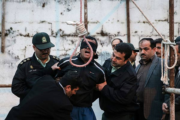This picture provided by ISNA, an semi-official news agency, taken on Tuesday, April 15, 2014 shows a blindfolded Iranian man Bilal being prepared to be hanged in public in the northern city of Nour, Iran. Bilal, who was convicted of killing Abdollah Hosseinzadeh, was pardoned by the victim's family moments before being executed. (AP Photo/ISNA, Arash Khamoushi)