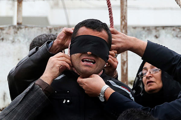 "<div class=""meta ""><span class=""caption-text "">This picture provided by ISNA, a semi-official news agency, taken on Tuesday, April 15, 2014 shows Samereh Alinejad, right, and her husband Abdolghani, left, removing the noose from the neck of blindfolded Bilal who was convicted of murdering their son Abdollah in the northern city of Nour, Iran. Bilal who was convicted of killing Abdollah Hosseinzadeh, was pardoned by the victim's family moments before being executed. (AP Photo/ISNA, Arash Khamoushi)</span></div>"