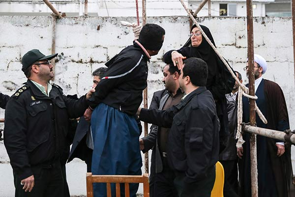 This picture provided by ISNA, an semi-official news agency, taken on Tuesday, April 15, 2014 shows Samereh Alinejad, right, slapping blindfolded Bilal, who was convicted of murdering her son Abdollah prior to his execution in public in the northern city of Nour, Iran. Bilal who was convicted of killing Abdollah Hosseinzadeh, was pardoned by the victim's family moments before being executed. (AP Photo/ISNA, Arash Khamoushi)