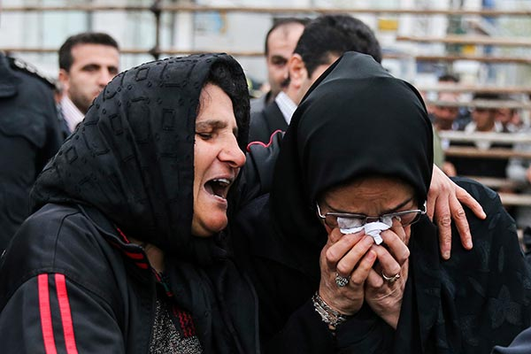 This picture provided by ISNA, a semi-official news agency, taken on Tuesday, April 15, 2014 shows Kobra, left, whose son Bilal was convicted of murdering a man, embracing Samereh Alinejad, mother of the victim, after she pardoned the murderer before his execution in public in the northern city of Nour, Iran. Bilal who was convicted of killing Abdollah Hosseinzadeh, was pardoned by the victim's family moments before being executed. (AP Photo/ISNA, Arash Khamoushi)