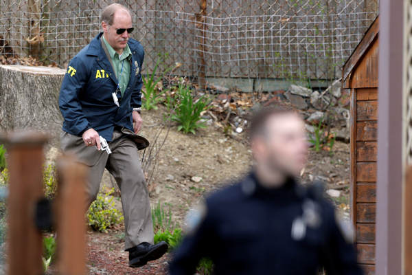 A police officer runs with his weapon drawn as he conduct a search for a suspect in the Boston Marathon bombings, Friday, April 19, 2013, in Watertown, Mass. Two suspects in the Boston Marathon bombing killed an MIT police officer, injured a transit officer in a firefight and threw explosive devices at police during a getaway attempt in a long night of violence that left one of them dead and another still at large Friday, authorities said as the manhunt intensified for a young man described as a dangerous terrorist. <span class=meta>(AP Photo&#47;Matt Rourke)</span>