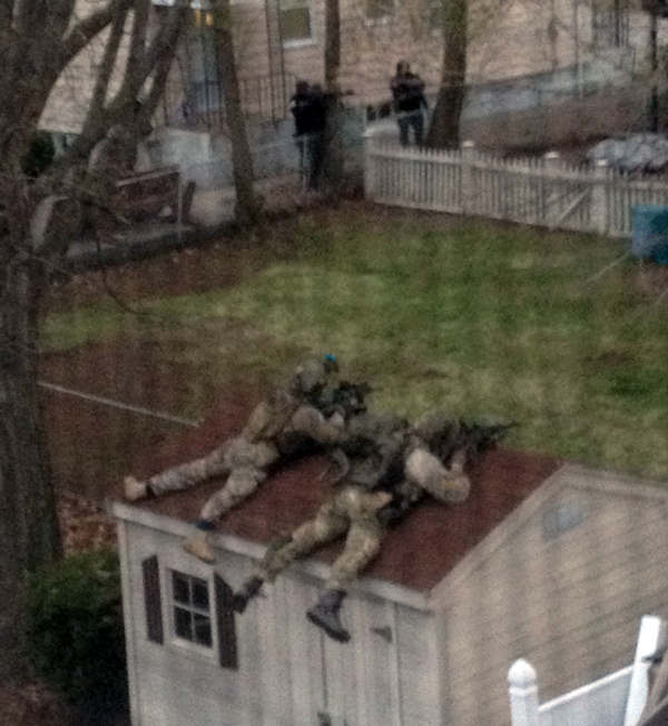 "<div class=""meta ""><span class=""caption-text "">This photo shot through a window screen provided by Samantha England, shows police in tactical gear outside England's home in Watertown, Mass. Friday, April 19, 2013. The two suspects in the Boston Marathon bombing killed an MIT police officer and hurled explosives at police in a car chase and gun battle overnight that left one of them dead and his brother on the loose, authorities said Friday as thousands of officers swarmed the streets in a manhunt that all but paralyzed the Boston area.  (AP Photo/Samantha England)</span></div>"