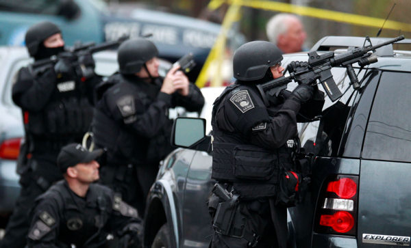 "<div class=""meta ""><span class=""caption-text "">Police in tactical gear surround an apartment building while looking for a suspect in the Boston Marathon bombings in Watertown, Mass., Friday, April 19, 2013. All residents of Boston were ordered to stay in their homes Friday morning as the search for the surviving suspect in the marathon bombings continued after a long night of violence that left another suspect dead.  (AP Photo/Charles Krupa)</span></div>"