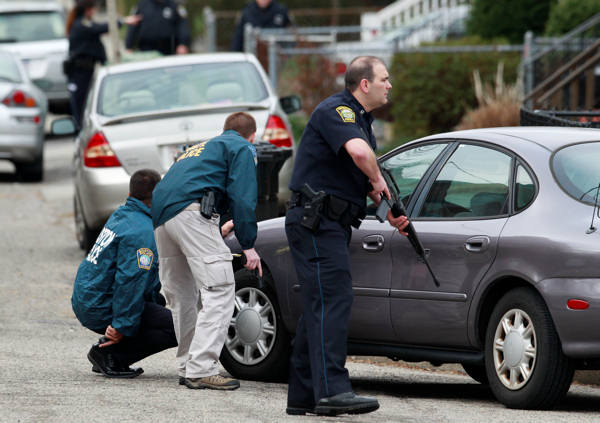 "<div class=""meta ""><span class=""caption-text "">Police surround a home while searching for a suspect in the Boston Marathon bombings in Watertown, Mass., Friday, April 19, 2013. The two suspects in the Boston Marathon bombing killed an MIT police officer and hurled explosives at police in a car chase and gun battle overnight that left one of them dead and his brother on the loose, authorities said Friday. (AP Photo/Charles Krupa)</span></div>"