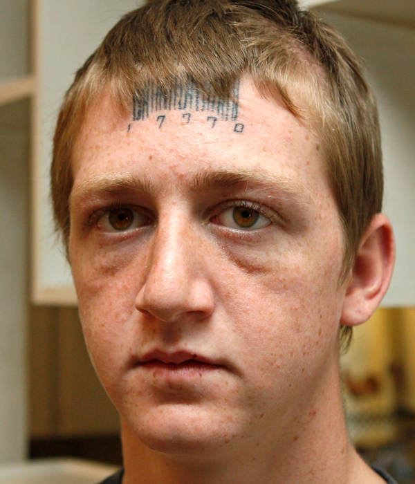 "Stetson Johnson, 18, poses for a photo in his home in Oklahoma City, Wednesday, May 4, 2011. His hair partially covers the tattoo on his forehead. Johnson said Wednesday that attackers forcibly tattooed the word ""rapest"" on his forehead, and he had the bar code tattooed over it in an attempt to hide it. (AP Photo/Sue Ogrocki)"