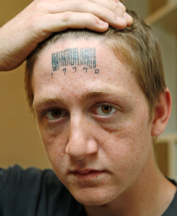 "Stetson Johnson, 18, holds back his hair to show a tattoo on his forehead in his home in Oklahoma City, Wednesday, May 4, 2011. The bar code on his forehead hides the word ""rapest"" which Johnson said Wednesday that attackers forcibly tattooed on his forehead, and he had the bar code tattooed over it in an attempt to hide it. The numbers are three 7s for lucky 7 and 10 for 2010. (AP Photo/Sue Ogrocki)"