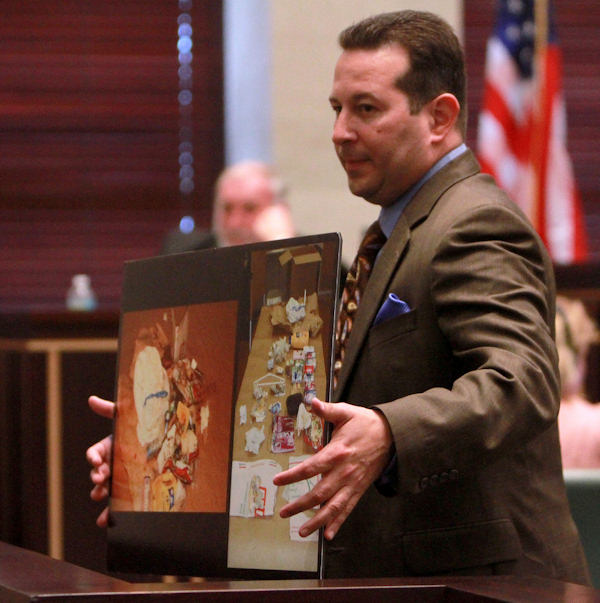 Defense attorney Jose Baez holds up photos during cross examination in the trial of Casey Anthony, Saturday, June 11, 2011, at the Orange County Courthouse, in Orlando, Fla. Anthony, 25, is charged with murder in the 2008 death of her daughter Caylee. (AP Photo/Joe Burbank, Pool)
