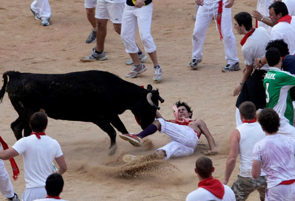 A reveler is hit by a calf in the bullring after the bull  run during the San Fermin fiestas on Thursday, July 8, 2010, in Pamplona, Spain. &#40;AP Photo&#47;Ivan Aguinaga&#41; <span class=meta>(AP Photo&#47;Ivan Aguinaga)</span>