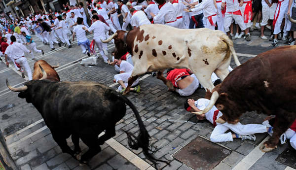 Revelers fall on the Estafeta corner in front of El Pilar ranch fighting bulls during the seventh run  of the San Fermin fiestas in Pamplona northern Spain, Tuesday July 13, 2010. &#40;AP Photo&#47;Alvaro Barrientos&#41; <span class=meta>(AP Photo&#47;Alvaro Barrientos)</span>