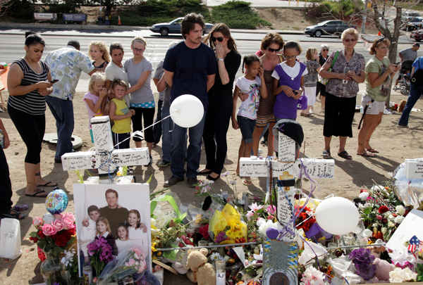 Actor Christian Bale, center, left, and his wife Sibi Blazic visit a memorial to the victims of Friday&#39;s mass shooting, Tuesday, July 24, 2012, in Aurora, Colo. Twelve people were killed when a gunman opened fire during a late-night showing of the movie &#34;The Dark Knight Rises,&#34; which stars Bale as Batman.  <span class=meta>(AP Photo&#47;Ted S. Warren)</span>