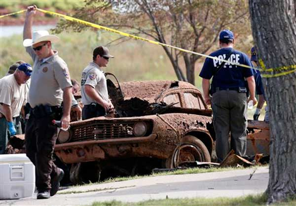 This Sept. 17, 2013, photo shows two cars recovered from Foss Lake, Okla. The Oklahoma State Medical Examiner's Office says authorities have recovered skeletal remains of multiple bodies in the Oklahoma lake where the two decades-old cars were pulled from the water by a dive team. (AP Photo/Daily Elk Citian, Laura Eastes)