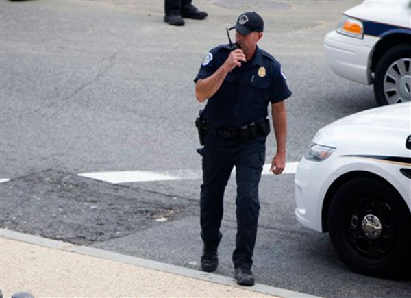 A Capitol Hill police officer talks on a radio after a report of a shooting on Capitol Hill in Washington, Thursday, Oct. 3, 2013. A police officer was reported injured after gunshots at the U.S. Capitol, police said Thursday.  <span class=meta>(AP Photo&#47; Evan Vucci)</span>