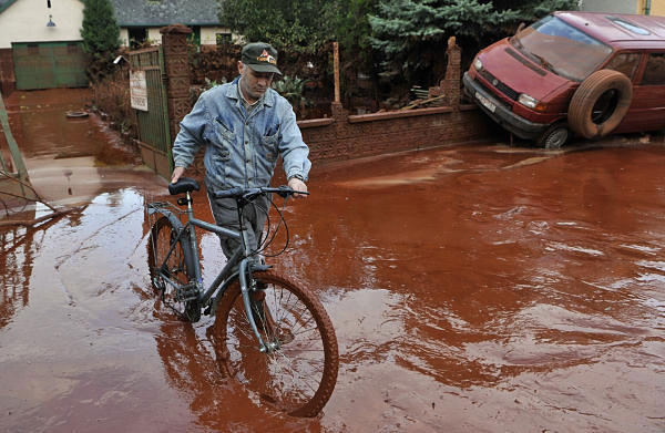 A Hungarian man pushes his bicycle in front of his home flooded with toxic mud in the town of Devecser, Hungary, Tuesday, Oct. 5, 2010. Monday&#39;s flooding was caused by the rupture of a red sludge  reservoir at an alumina plant in western Hungary and has affected seven towns near the Ajkai Timfoldgyar plant in the town of Ajka, 100 miles &#40;160 kilometers&#41; southwest of Budapest. <span class=meta>(AP Photo)</span>