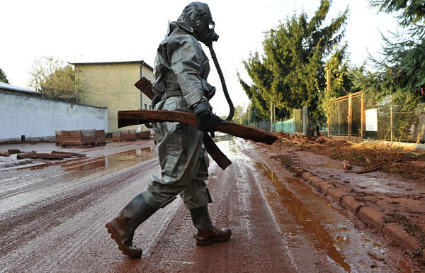 A Hungarian soldier, wearing a chemical protection gear, cleans a street flooded by toxic in the town of Devecser, Hungary, Tuesday, Oct. 5, 2010. Monday&#39;s flooding was caused by the rupture of a red sludge  reservoir at an alumina plant in western Hungary and has affected seven towns near the Ajkai Timfoldgyar plant in the town of Ajka, 100 miles &#40;160 kilometers&#41; southwest of Budapest.  <span class=meta>(AP Photo)</span>
