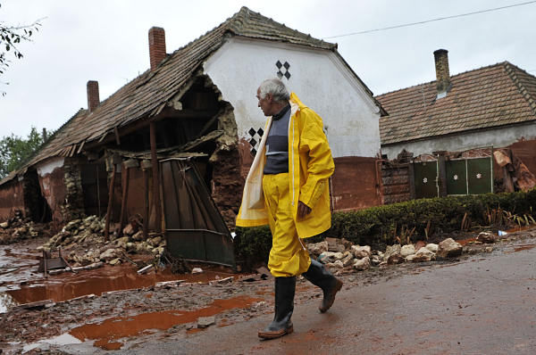 A villager walks in front of houses destroyed by a flood of toxic mud in Kolontar, Hungary, Wednesday, Oct. 6, 2010. Emergency workers and construction crews on Wednesday swept through the Hungarian towns hardest hit by a flood of toxic sludge, trying to clear roads and homes of acres &#40;hectares&#41; of deep red mud and caustic water. Hundreds of people were evacuated after the disaster Monday, when a gigantic sludge reservoir burst its banks at metals plant in Ajka, a town 100 miles &#40;160 kilometers&#41; southwest of Budapest, the capital. The torrent inundated homes, swept cars off roads and damaged bridges, disgorging an estimated 1 million cubic meters &#40;35.3 million cubic feet&#41; of toxic waste onto several nearby towns.  <span class=meta>(AP Photo)</span>