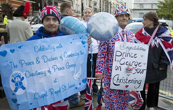 Royal wellwishers gather and display their home made placards and greetings to the media, as they wait outside St James&#39;s Palace, for the christening of Britain&#39;s Prince George, in London, Wednesday, Oct. 23, 2013. Prince William and his wife Kate have asked seven people to be godparents to their son, Prince George, who will be christened at a major royal family gathering Wednesday, palace officials said.  <span class=meta>(AP Photo&#47;Alastair Grant)</span>