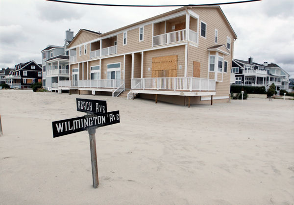 A street sign is partially buried in sand Tuesday morning, Oct. 30, 2012, in Cape May, N.J., after a storm surge from Sandy pushed the Atlantic Ocean over the beach and across Beach Avenue.  <span class=meta>(AP Photo&#47;Mel Evans)</span>