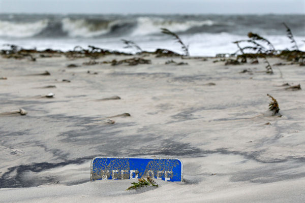 A keep off the dunes sign is buried Tuesday morning, Oct. 29, 2012, in Cape May, N.J., after a storm surge from superstormSandy pushed the Atlantic Ocean over the beach and into the streets. The storm that made landfall in New Jersey on Monday evening with 80 mph sustained winds killed at least 16 people in seven states, cut power to more than 7.4 million homes and businesses from the Carolinas to Ohio, caused scares at two nuclear power plants and stopped the presidential campaign cold.  <span class=meta>(AP Photo&#47;Mel Evans)</span>