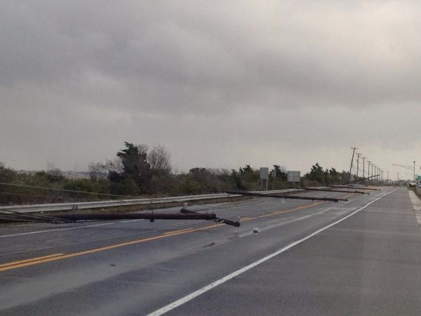Utility poles knocked down by strong winds from Hurricane Sandy lay on a roadway in Longport, New Jersey.