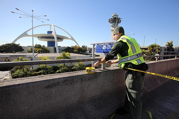 A police officer closes a road at the Los Angeles International Airport on Friday Nov. 1, 2013, after shots were reporter in Terminal 3, prompting authorities to evacuate the terminal and stop flights headed for the city from taking off from other airports.  <span class=meta>(AP Photo&#47;Ringo H.W. Chiu)</span>