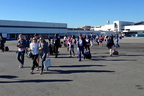 In this photo provided by John Forstrom, which has been authenticated based on its contents and other AP reporting, people walk across the tarmac after being evacuated from Los Angeles International Airport, Friday, Nov. 1, 2013. Shots were fired Friday at Los Angeles International Airport, prompting authorities to evacuate a terminal and stop flights headed for the city from taking off from other airports. <span class=meta>(AP Photo&#47;John Forstrom)</span>