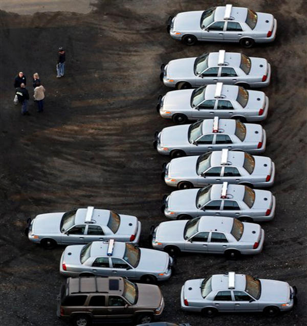 Police vehicles are lined up near a triage near Sandy Hook Elementary School in Newtown, Conn., where authorities say a gunman opened fire inside an elementary school in a shooting that left 27 people dead, including 18 children, Friday, Dec. 14, 2012. (AP Photo/Julio Cortez)