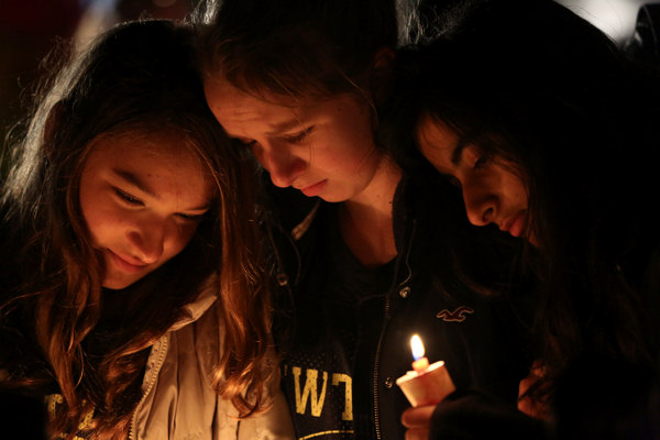 Kate Suba, left, Jaden Albrecht, center, and Simran Chand pay their respects at one of the makeshift memorials in honor of the victims of the Sandy Hook Elementary School shooting, Sunday, Dec. 16, 2012, in Newtown, Conn. A gunman opened fire at the school on Friday, killing 26 people, including 20 children before killing himself on Friday.  <span class=meta>(AP Photo&#47;Mary Altaffer)</span>