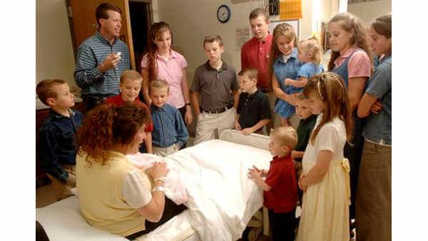 Michelle Duggar, left, is surrounded by her children and husband Jim Bob, top left, while she holds her newborn daughter, Jennifer Danielle, Thursday, Aug. 2, 2007 in Rogers, Ark. Jennifer Danielle was born at 10:01 a.m., weighed 8 lbs 8 oz, was 21 inches long, and is the 17th child born to Michelle and Jim Bob Duggar. (AP Photo/Beth Hall)