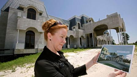 In a Friday, June 11, 2010 photo, realtor Lorraine Barrett looks at a rendering of what the unfinished mansion nicknamed Versailles will look like when completed, in Windermere, Fla. The mansion is currently up for sale as is by owner and timeshare tycoon David Siegel. (AP Photo/John Raoux)